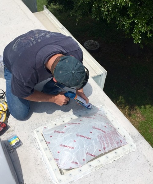 And finally, sealing the seams and screws with more caulk. Best part? It's on the roof, so neatness does not count. Which is good, because both of us are pretty lousy at this.